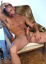 Buff porn star CJ Madison sits back relaxed, showing off his bulging muscles, f